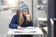 Junge Frau mit Kaffee und Zeitung