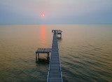wooden bridge laying into the sea at scenery sunset