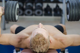 Muscular young man shirtless, lifting dumbbells training pecs on gym bench