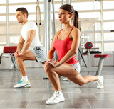 Young couple with sport body doing workout at the gym.They stretching legs.