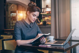 Fototapety Young businesswoman in gray dress sitting at table in coffee shop and reading book. On table laptop, smartphone and cup of coffee. Student learning online. Freelancer working. Online education.