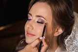 Wedding make up for beautiful bride with pure skin. Makeup artist makes makes make-up with brush in hand