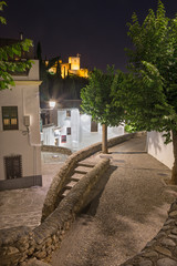 GRANADA, SPANI - MAY 28, 2015: The aisle in Albayzin distrit at night and Alhambra in the background.