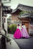 Fototapety A couple women wander through the traditional style houses of Bukchon Hanok Village in Seoul, South Korea.