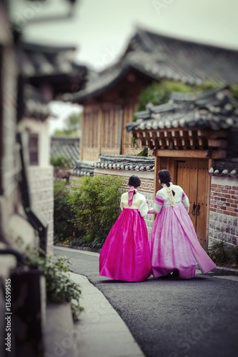 A couple women wander through the traditional style houses of Bukchon Hanok Village in Seoul, South Korea Poster