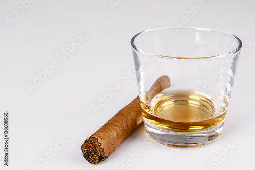 expensive drink of whisky or rum with cigar on white