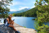 Girl sitting and relaxing on top of mountain rock on a hiking trip looking at her iphone. Bear Lake. Rocky Mountains National Park, Colorado ,USA. - 136613196