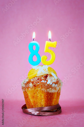 Poster Muffin with burning birthday candles as number eighty five on pink background