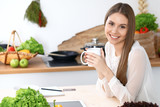 Young happy woman is holding white cup and looking at the camera while sitting at wooden table in the kitchen among green vegetables. Housewife is looking for a new recipe or having morning coffee