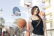 Defiant woman holding a basket ball on a sports playground, outdoors on a sunny day.