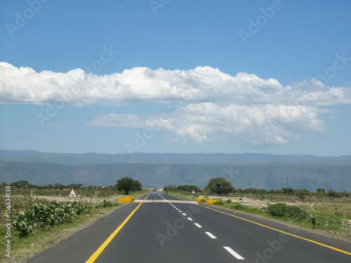 Fotobehang Overige Straight modern highway in savanna vanishing in horizon against mountain and blue sky background at sunny day. Tanzania, Africa.