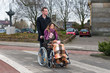 Man pushing a woman in a wheelchair at a zebra crosssing