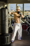 Shirtless handsome muscular young man in gym kicking punching bag, wearing boxing gloves and helmet