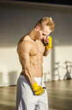 Shirtless muscular young man standing with jumping rope in gym, looking down at himself