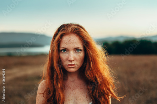 Portrait of red haired woman outdoors - 136695394