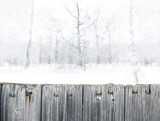 Blurred winter forest background in snow. Old wooden fence on the foreground