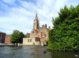 Church and vintage building as seen from cruising boat, Bruges, Belgium