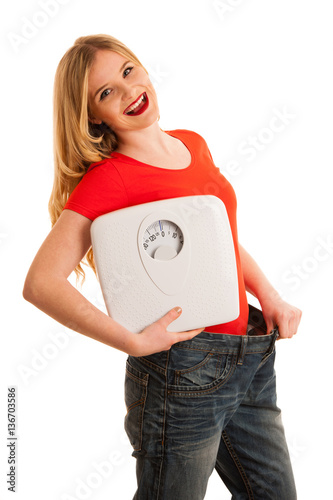 Happy womman holding a scale and too big trousers as she lost we