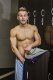 Shirtless muscular young male athlete caught semi naked in gym changing room, embarassed