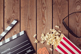 Movie clapper board, 3d glasses and popcorn on wooden background. Cinema concept.Top view from above - 136707385