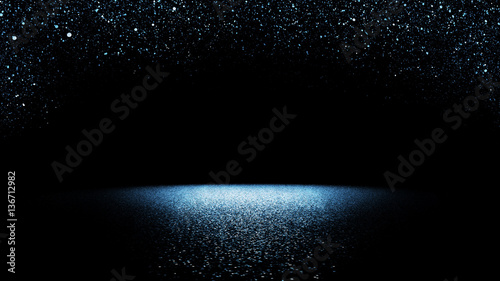 glitter background - twinkling blue glitter falling on a flat surface lit by a bright spotlight