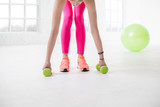 Woman lifting dumbbells in the white room. Close up view on the hands