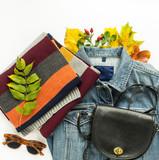 Stylish autumn look. Autumn fashion, woman autumn outfit on white background. Blue denim jacket , retro sunglasses, black crossbody bag, stripe scarf. Flat lay, top view