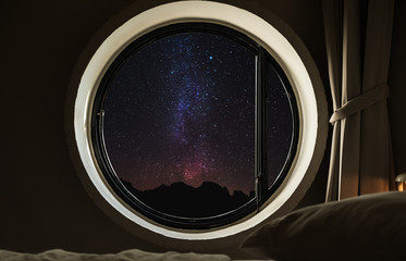 Round circle window frame with night sky full of stars with milky way