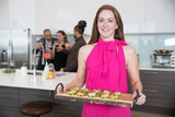 Beautiful redhead hostess serving prawns appetizer at dinner party with group of friends