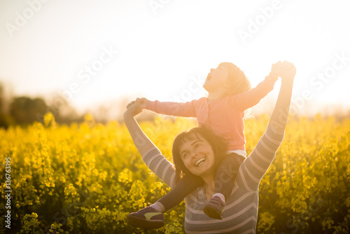 Cute joyous kid girl riding on shoulders of her mother Poster