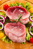 Raw meat on cutting board and vegetables