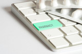 Tabletten und ein Computer mit der Taste für Online Apotheke