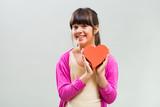 Little girl holding heart shape on grey background.
