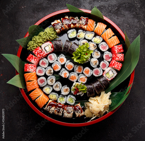 Papiers peints Sushi bar Japanese cuisine. Sushi set on a round wooden plate and dark concrete background.