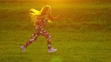 Pretty young girl happily running outdoors in fileds on sunset, slow motion.