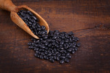 Black beans in scoop on wooden background