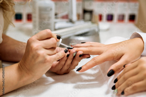 Fotobehang Manicure Manicure process in beauty salon, close up. Black nails.