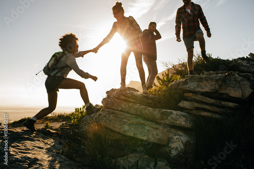 Young people on mountain hike at sunset