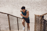 Fit young man running up the steps at beach