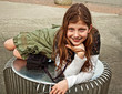Cute Caucasian 9 year old girl curled on on a table outdoors and smiling.