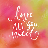 Love is all you need. Inspirational saying about love. Modern calligraphy - white text on pink and green watercolor texture.