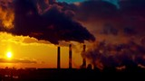 Dramatic sunset clouds over industrial plant pipes time-lapse
