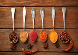 Spices in spoons on a wooden background