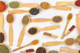 Different spices in wooden spoons on white background