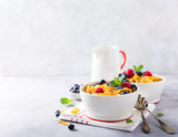 Healthy breakfast with corn flakes, berries and milk on light gray background. Copy space.