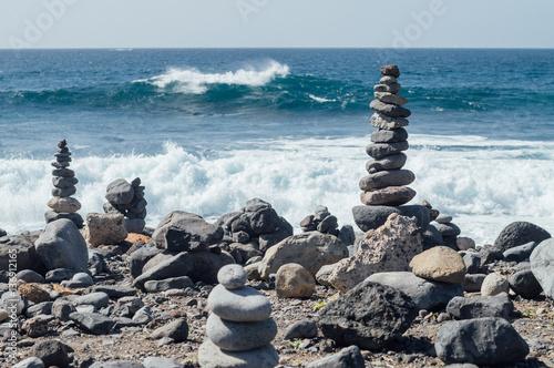 Foto op Canvas Zen Cairn against ocean wave, zen concept