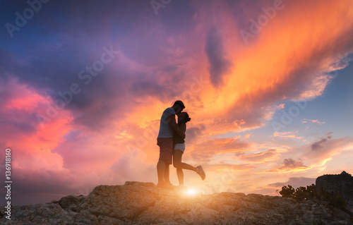 Staande foto Oranje eclat Silhouettes of a hugging and kissing man and girlfriend on the mountain peak at sunset. Man and woman. Landscape with silhouette of people against colorful sky. Couple, lovers, relationship