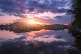 River against colorful sky with clouds and rocks at sunset in summer. Beautiful landscape with lake, mountains, sunlight and blue cloudy sky reflected in water at twilight. Nature. Reflection in water