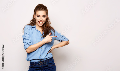 cheerful girl in denim styling on solid background