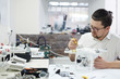 Portrait of modern man working on repairing tech, assembling expensive drone on white table with assorted tools